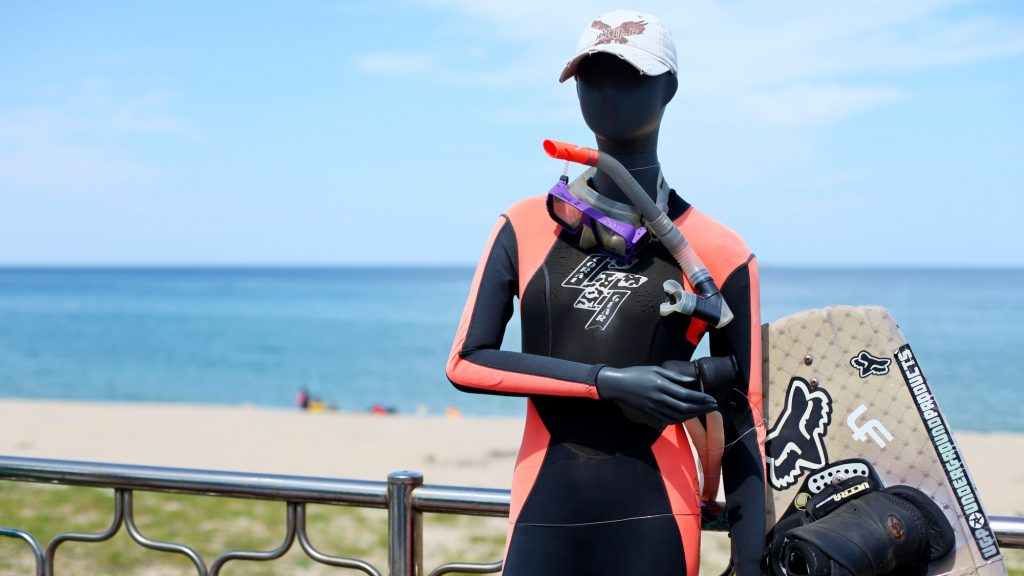 A picture of a manikin dressed in a wet suit in a beach in Korea.
