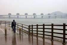 A picture of a cyclist riding through the snowy and rainy day near the Ipo-bo weir.