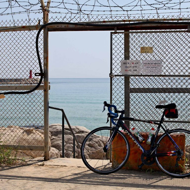 A bicycle sits near a barb wire fence on the Gangwon Bicycle Path in Korea.