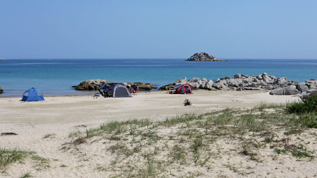 A few tents perched on an empty beach along South Korea's East Coast Bike Route.