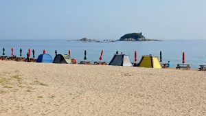 A few tents and umbrellas sit on a beach near the city of Sokcho in South Korea.