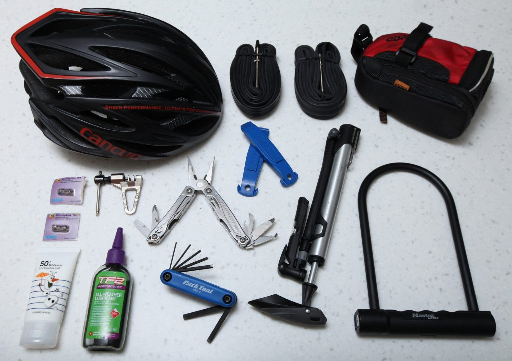 A picture of a helmet, tubes, saddle bag, quick links, chain breaker, multi-tool, tire levers, air pump, lock, sunscreen, lube, hex wrenches.