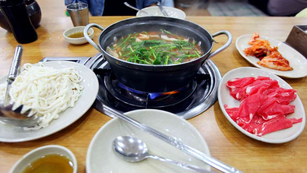 A picture of noodles cooking in a pot in a restaurant in Korea.