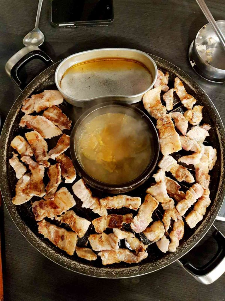 A picture of samgyeopsal (삼겹살), or strips of pork belly, simmering around a pot of soy bean soup (된장찌개).