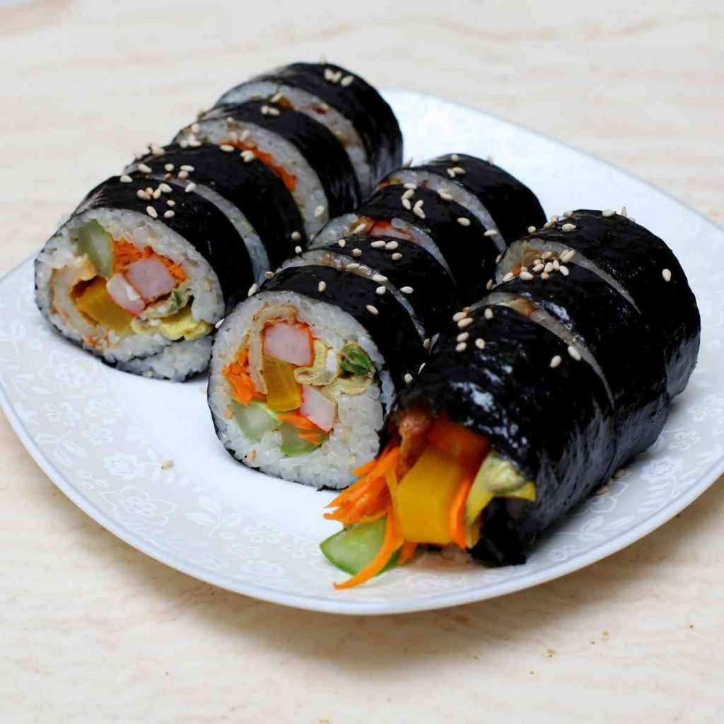 A few rolls of gimbap (김밥), a traditional Korean meal, sit on a plate.