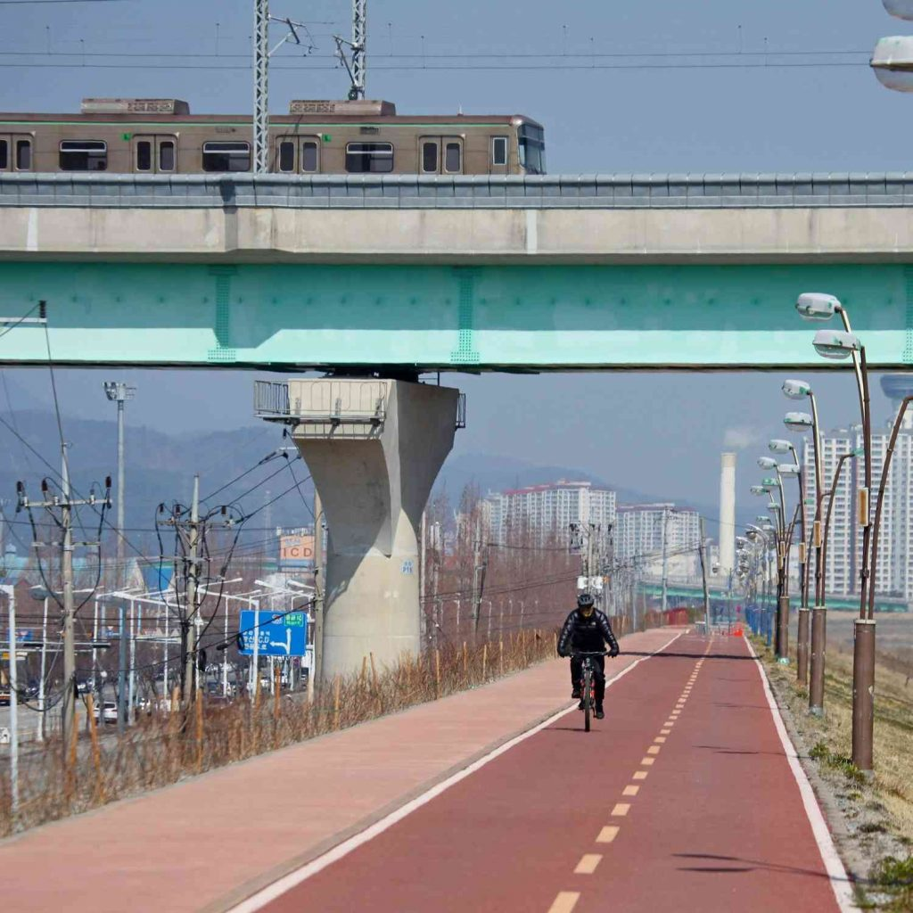 A picture of a Busan subway train crossing over the bike path in the city of Yangsan along the Cross-Country bike path.