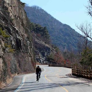 A bicycle rider rides down a mountain on the Saejae Bicycle Path in Korea.