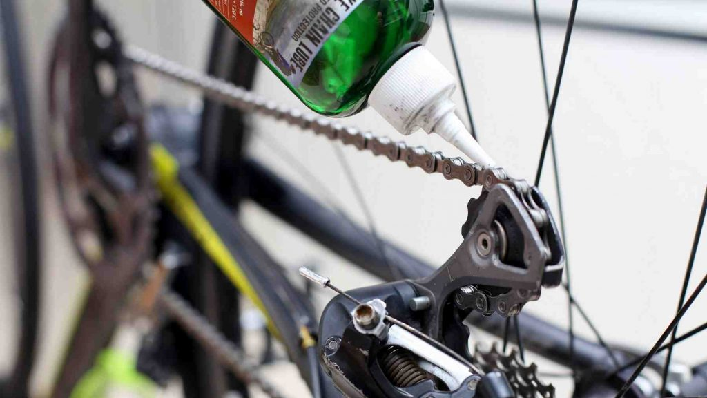 A picture of a bike chain being lubricated.
