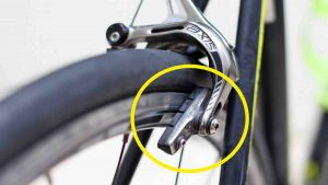 A picture of a misaligned brake pad on a bicycle wheel.