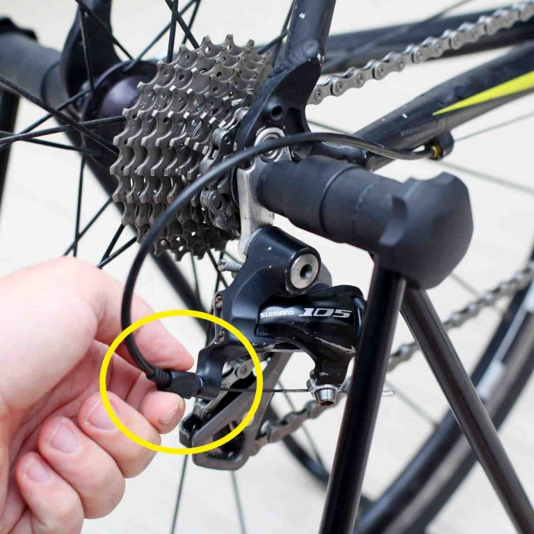 A picture of a hand turning the rear derailleur's barrel adjuster on a bicycle.