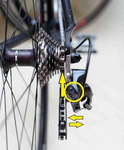 A picture of a bicycle's rear derailleur with its limit screws highlighted.