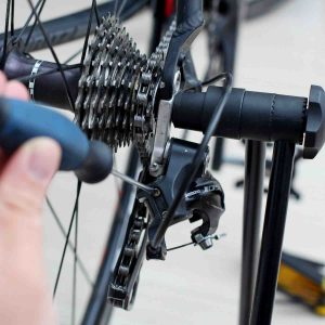 A picture of a screwdriver turning the limit screws on a bicycle's rear derailleur.