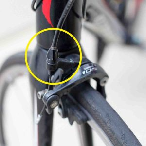 A picture of bicycle rim brakes with the barrel adjuster circled.