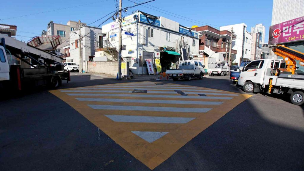 A picture of an yellow painted intersection in a back street of South Korea.