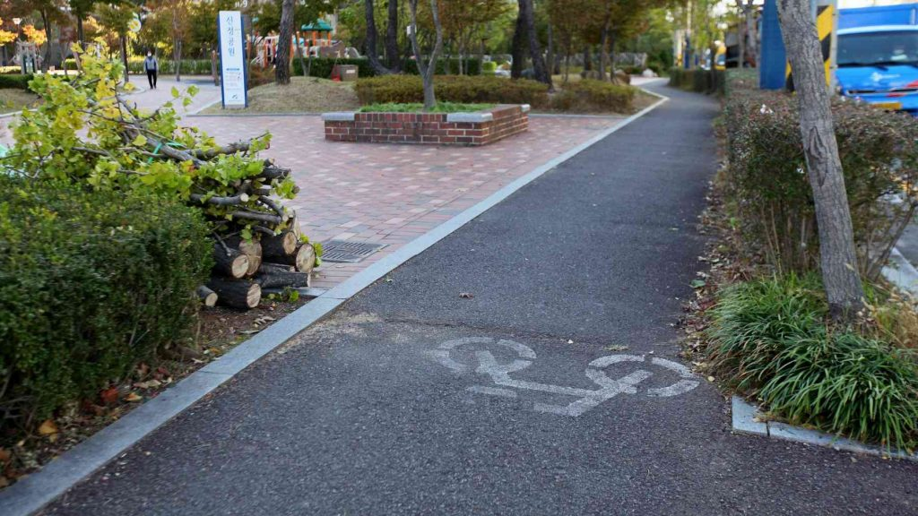 A picture of a sidewalk with a bike path in South Korea.