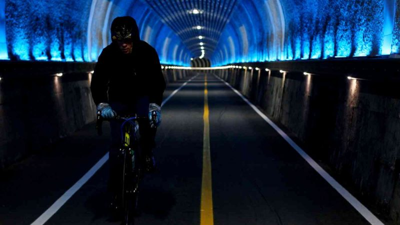 A picture of a cyclists riding through the decommissioned train tunnels of the Namhangang Bicycle Path.