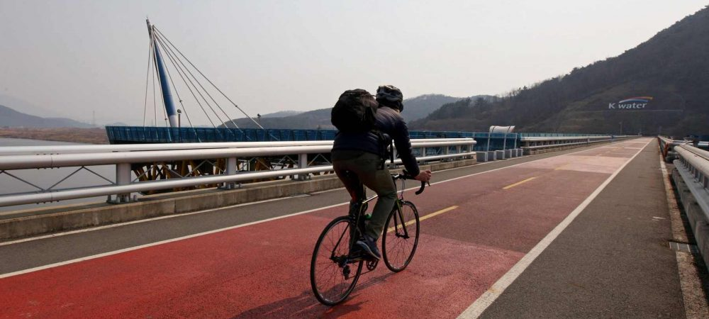 A bike rider crosses Dalseong-bo (달성보) near the city of Namji in South Korea.